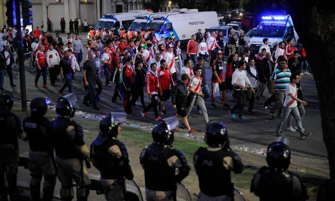 Forças de segurança acompanham saída de torcedores do River Plate do estádio Monumental, após adiamento, no sábado. Foto: Javier Gonzalez Toledo / AFP