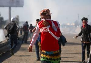 Imigrante corre e protege o rosto do gás de pimenta lançado por agentes de fronteira, em Tijuana Foto: HANNAH MCKAY / REUTERS