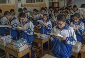 """Alunos fazem sessão de leitura conjunta na escola de ensino médio Huining Nº1: nas paredes da instituição, cartazes afirmam que sacrifício para entrar na faculdade não se compara a """"uma vida inteira de sofrimento"""" Foto: GILLES SABRIÉ / NYT"""