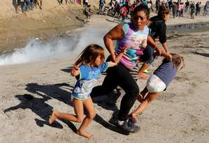 Família de Honduras corre do gás lacrimogêneo lançado por autoridades americanas contra caravana migrante na fronteira Foto: KIM KYUNG-HOON / REUTERS