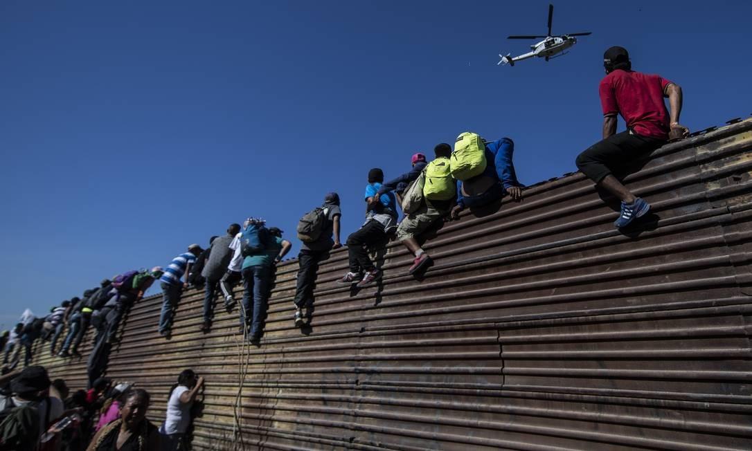 Grupo de centroa-americanos escalam cerca de metal na tentatia de chegar do México aos EUA Foto: PEDRO PARDO / AFP