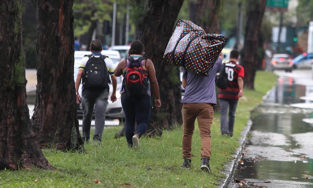 Com o trânsito toltamente parado por causa de alagamentos, passageiros saltam dos ônibus e caminham na Lagoa Foto: Fabiano Rocha / Agência O Globo