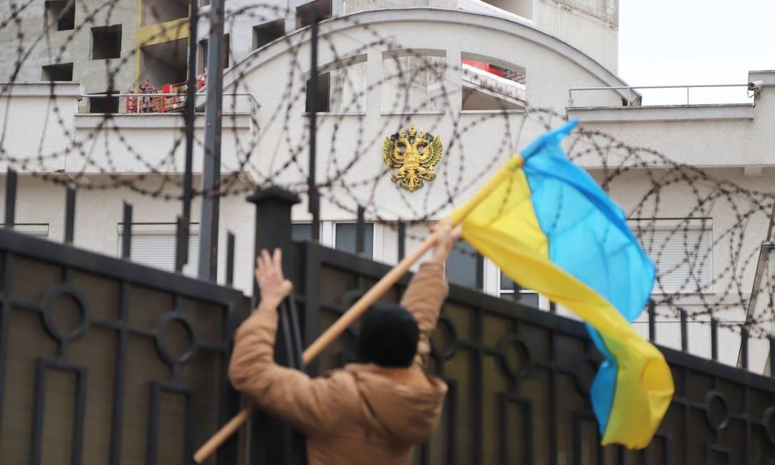 Manifestante escala grade de consulado russo em Odessa com bandeira da Ucrânia Foto: ALEKSANDR GIMANOV / AFP