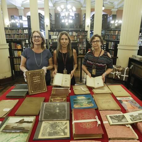 Maria José, Carla Rossana e Mônica mostram parte dos 861 itens recuperados pela PF e entregues à Biblioteca Nacional Foto: Gabriel de Paiva / Agência O Globo