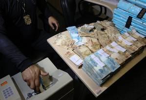 Policial federal conta parte do dinheiro que foi apreendido na operação que levou dez deputados estaduais à prisão Foto: Pedro Teixeira / Agência O Globo