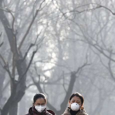 Chinesas usam máscara em parque de Pequim: poluição atmosférica é problema frequente no país Foto: Andy Wong / AP/19-12-2016