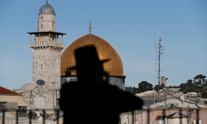 Judeu ultraortodoxo com o Domo da Rocha da Mesquita de al-Aqsa ao fundo, em Jerusalém Foto: AHMAD GHARABLI / AFP