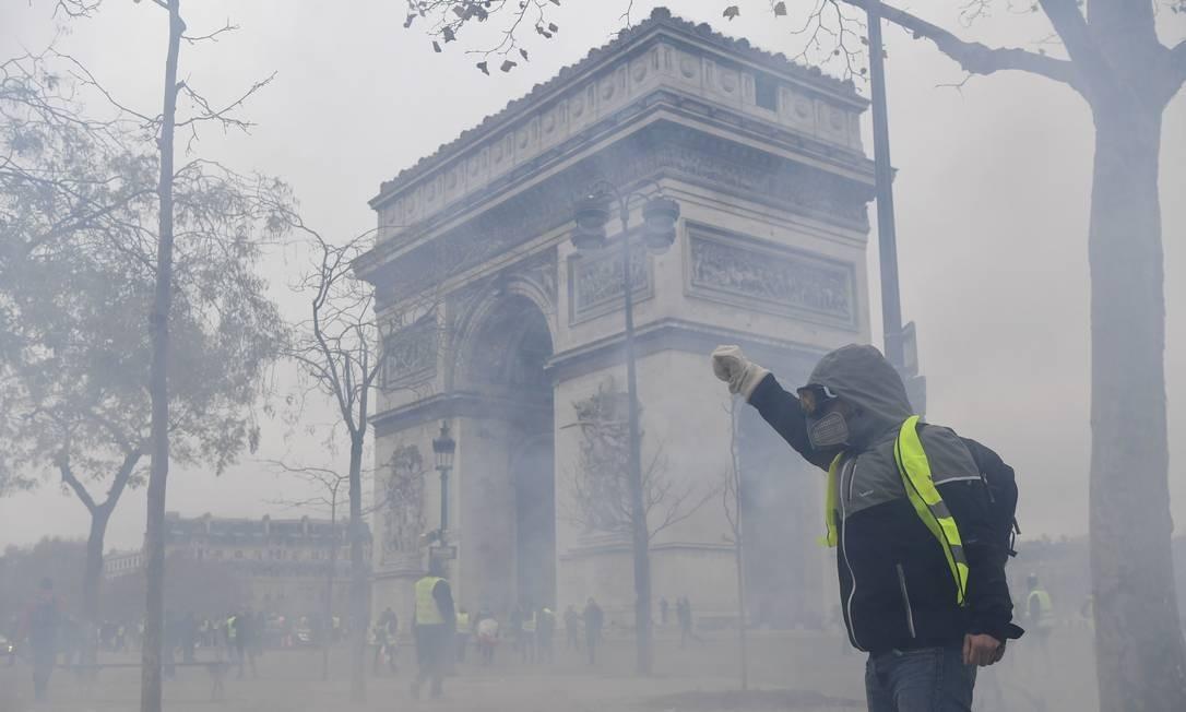 Manifestante próximo ao Arco do Triunfo, um dos principais cartões-postais de Paris Foto: ALAIN JOCARD / AFP