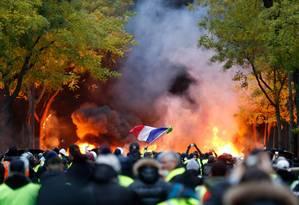 Manifestante agita a bandeira da França diante de pilha de pneus queimados em Paris, durante manifestação dos coletes amarelos Foto: GEOFFROY VAN DER HASSELT / AFP