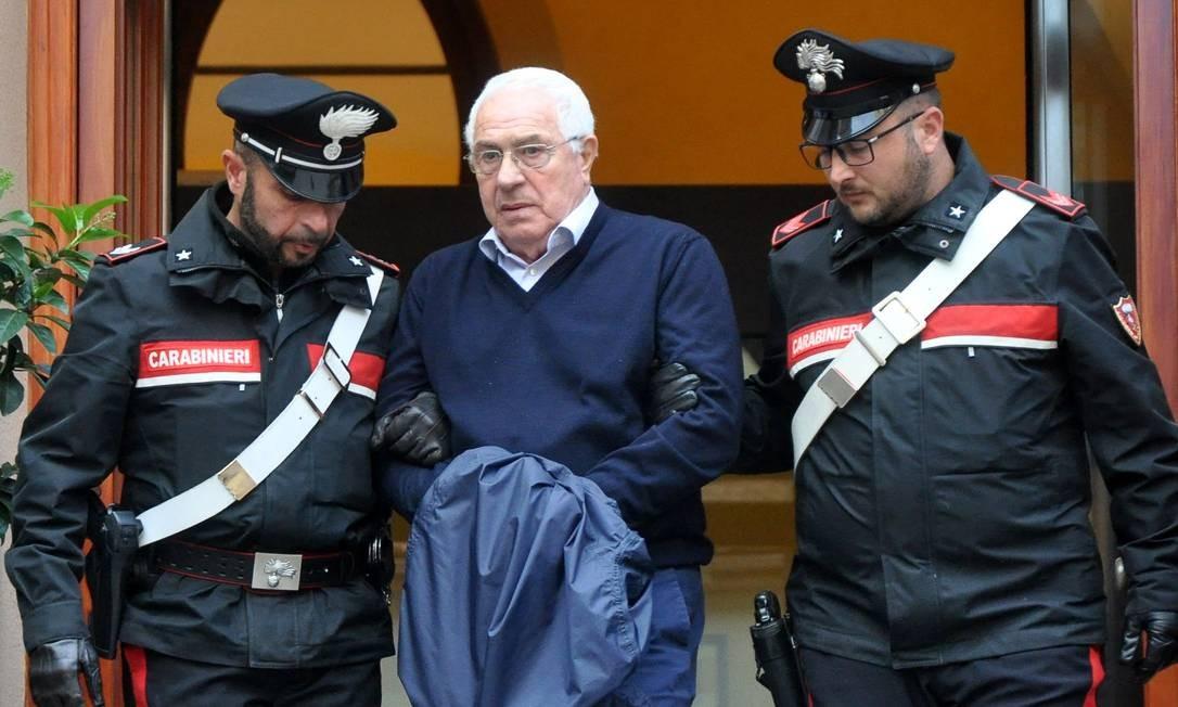 Settimo Mineo é escoltado por agentes da carabinieri ao deixar delegacia algemado em Palermo Foto: ALESSANDRO FUCARINI / AFP