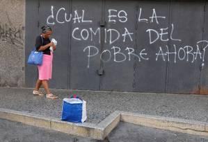 """""""Qual é a comida do pobre agora"""", lê-se em pichação de muro em Caracas Foto: MARCO BELLO / REUTERS"""