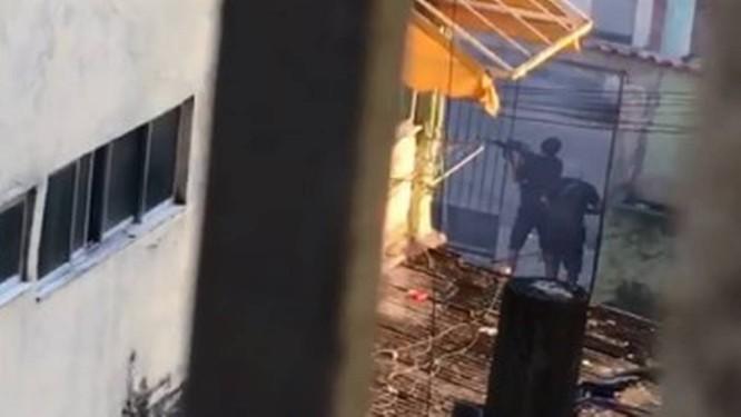 Homens posicionados em frente a um portão fazem disparos no Quitungo Foto: Reprodução de vídeo