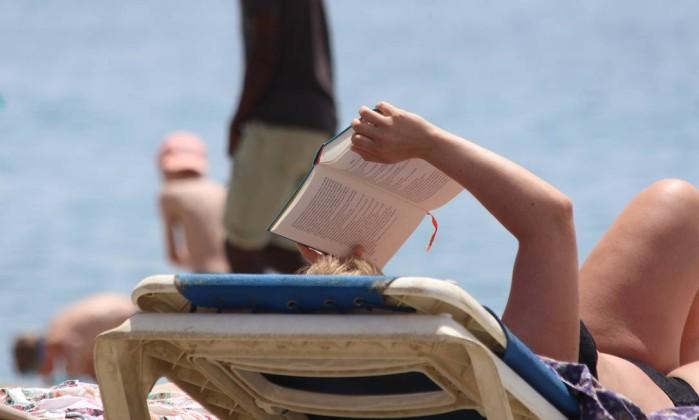 No verão, tape o sol na cara com um livro e aproveite para pôr a leitura em dia Foto: Pixabay