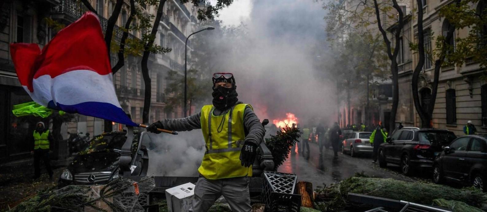 Manifestante de colete amarelo exibe a bandeira francesa durante o protesto em Paris Foto: ALAIN JOCARD / AFP/1-12-2018