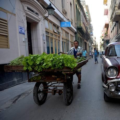 Vendedor de frutas e vegetais anda pelas ruas de Havana, em Cuba Foto: YAMIL LAGE / AFP