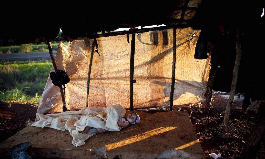 Índios Caiowás do acampamento Apika'y, à beira da BR 463. Eles esperam para voltar à sua terra original que fica a alguns metros dali, do outro lado da rodovia. Eles já haviam sido várias vezes expulsos de suas terras pelo fazendeiro que plantava cana-de-açúcar no local. No estado do Mato Grosso do Sul, existem quase 20 grupos como os Apika'y morando às margens de rodovias. Na foto, a índia Sandriele. Dourados. 25/11/2011. Foto: Filipe Rodondo/ Editora Globo. Foto: Filipe Rodondo / Agência O Globo