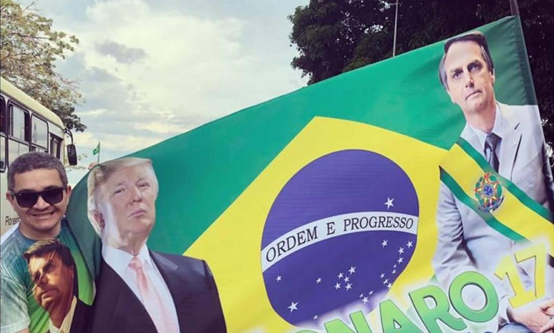 Alecxandro Carreiro, indicado para a Apex, segura faixa com imagens de Bolsonaro e Trump Foto: Reprodução