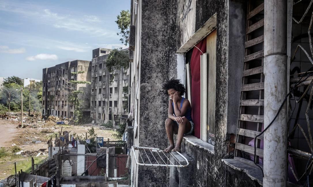 Sentada no parapeito da janela, observa a rua. Ela vive com sete irmãos num dos apartamentos dos cinco edifícios inacabados de uma ocupação em Campo Grande, na Zona Oeste do Rio (Peter Bauza) 02.11.2017 Agência O Globo