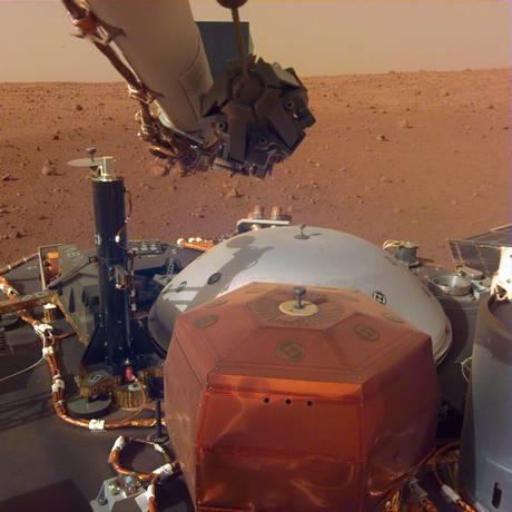 Imagem mostra os principais instrumentos da missão InSight ainda descansando no deque da sonda antes de serem postos na superfície pelo braço robótico da nave, acima deles: sismômetro está instalado no grande domo cinza à frente Foto: NASA/JPL-Caltech