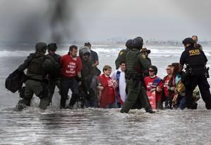 Ativistas pelos imigrantes que esperam em Tijuana, no México, são detidos na praia Imperial, em San Diego, na Califórnia Foto: GUILLERMO ARIAS / AFP