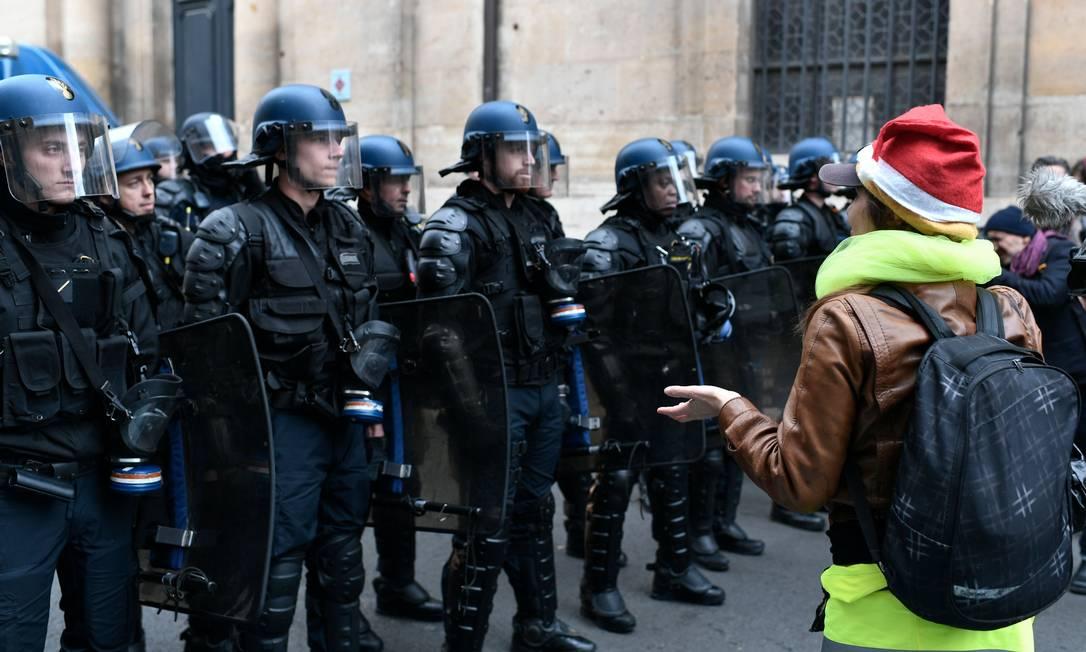 Manifestante vestida em apoio a movimento de coletes amarelos na frente de policiais durante marcha de estudantes em Paris Foto: STEPHANE DE SAKUTIN / AFP