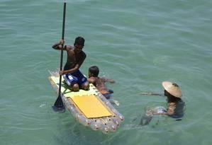 Criatividade. Jovens brincam com a prancha de stand up paddle feita de PET por alunos da Uerj: ideia que veio do Sul Foto: Gabriel de Paiva / Agência O Globo