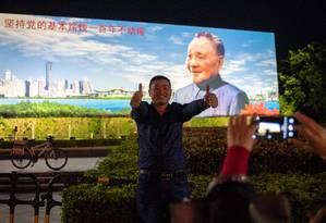 Homem posa em frente a outdoor mostrando Deng Xiaoping, que iniciou as reformas econômicas no país há 40 anos Foto: NICOLAS ASFOURI / AFP