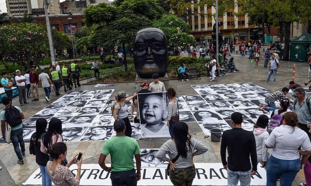 """Retratos de imigrantes e refugiados venezuelanos são colocados no chão da praça Botero, em Medellín, como parte da campanha """"Somos Panas"""" (Somos parças) Foto: JOAQUIN SARMIENTO / AFP/17-12-2018"""