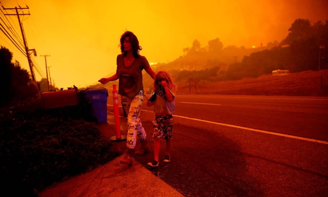 Gabi e Jonah Frank caminham em rodovia na Califórnia, onde incêndio se alastrou, ameaçando a casa deles em Malibu (9/11/2018) Foto: ERIC THAYER / REUTERS
