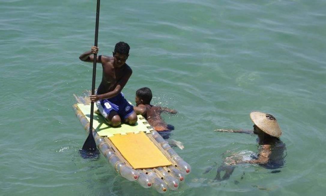 Criatividade. Jovens brincam no mar com a prancha de stand up paddle feita de PET por alunos da Uerj: ideia que veio do Sul Foto: Gabriel de Paiva