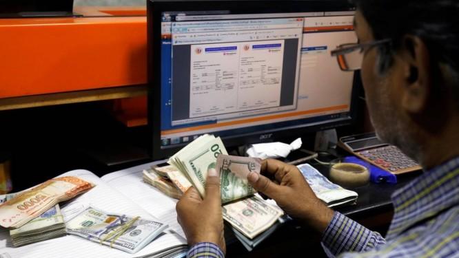 Homem conta cédulas de dólar, a moeda oficial dos Estados Unidos Foto: Akhtar Soomro / Reuters