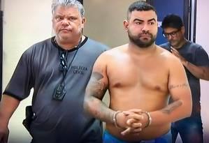 Policial conduz Renatinho Problema (sem camisa), preso em Guapimirim Foto: Reprodução / TV Globo