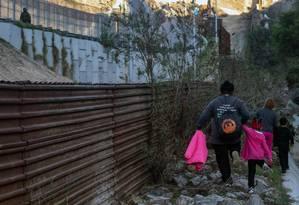 Migrantes centro-americanos buscam local de passagem na barreira na fronteira entre México e Estados Unidos Foto: GUILLERMO ARIAS / AFP