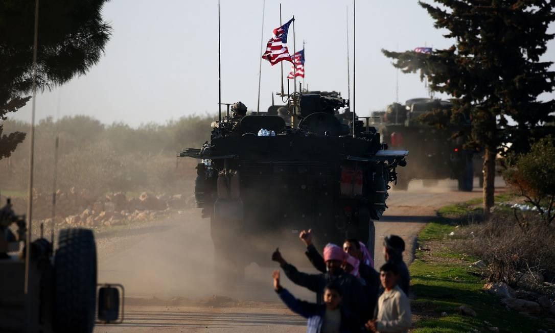 Um comboio de veículos blindados americanos perto da cidade de Yalanli, no Norte da Síria, passa ao lado de um grupo de pessoas que pede carona Foto: DELIL SOULEIMAN / AFP 5-03-17