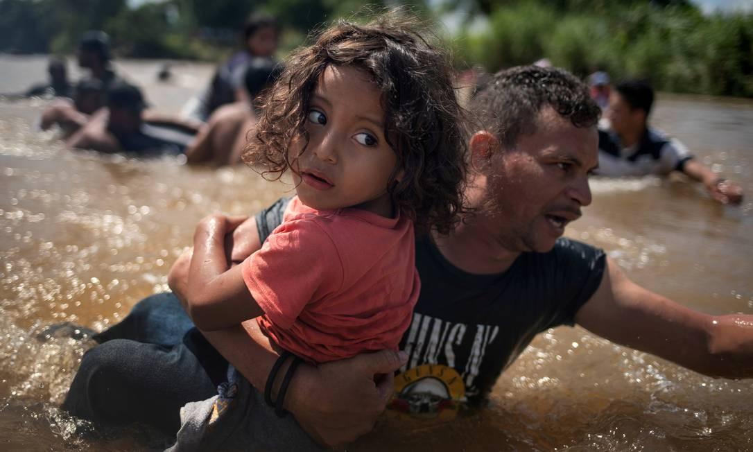 Pai e filha atravessam rio durante viagem de Honduras até os Estados Unidos; eles participavam da caravana migrante centro-americana que partiu de San Pedro Sula em outubro passado Foto: ADREES LATIF / REUTERS