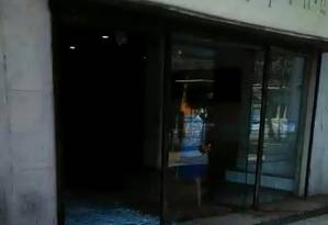 A porta do Shopping Guadalupe estilhaçada por tiros Foto: Reprodução de vídeo