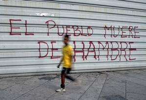 """""""O povo morre de fome"""", afirma pichação em rua de Caracas, na Venezuela Foto: Federico Parra / AFP"""
