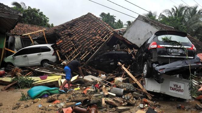 Moradora tenta retirar pertences dos escombros de sua casa, após tsunami Foto: Antara Foto / Reuters
