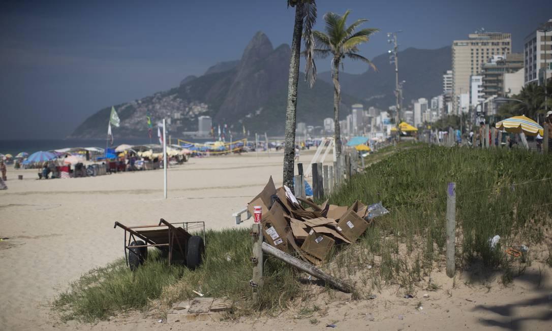 Carrinho ao lado de pedaços de papelão e lixo na vegetação da Praia de Ipanema Foto: Márcia Foletto / Agência O Globo
