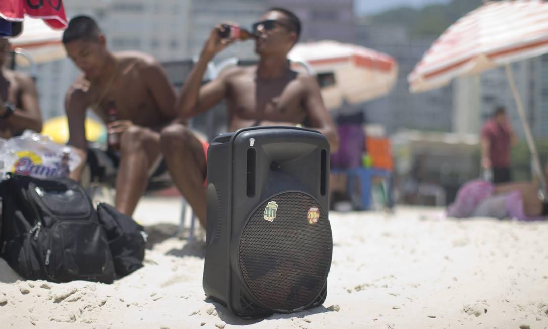 Banhistas levam caixa de som para ouvir música na areia, no Leme Foto: Márcia Foletto / Agência O Globo