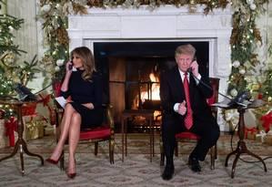Presidente dos EUA, Donald Trump, e a primeira-dama, Melania Trump, atendem telefonemas de Natal na Casa Branca Foto: SAUL LOEB / AFP