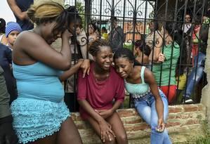 Choro sofrido.Mulheres lamentam crime envolvendo parentes em Cali, na Colômbia, em 2017; acordo de paz não retirou vulneráveis da pobreza e da violência Foto: LUIS ROBAYO / Agência O Globo