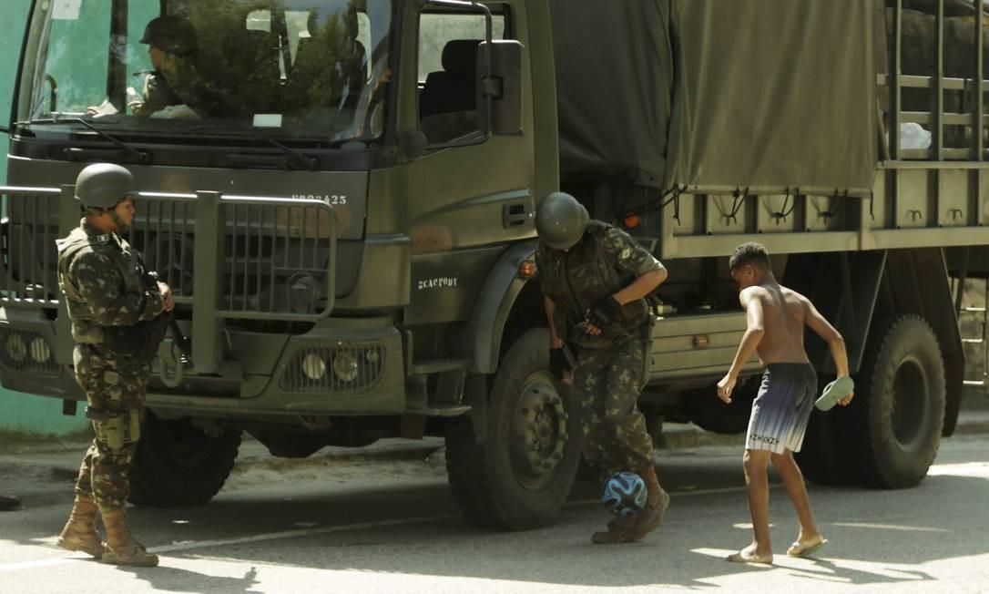 Forças Armadas fazem operação no Complexo do Lins. A autoestrada Grajaú-Jacarepaguá ficou fechada durante toda a manhã. Soldado brinca com crianças na auto-estrada. Foto: Gabriel de Paiva / Agência O Globo