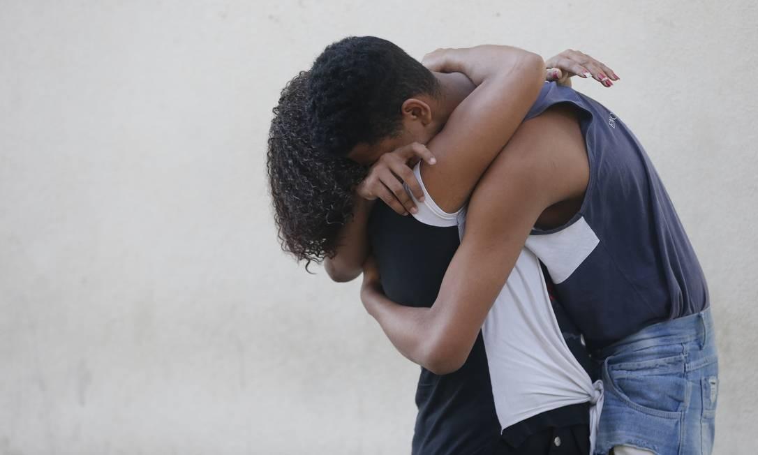 Três dos 70 presos em megaoperação no complexo do alemão deixam o Presídio de Benfica. Marcia da Silva Santos (preto) abraça o filho Patrick. Foto: Domingos Peixoto / Domingos Peixoto