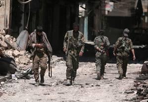 Combatentes das Forças Democráticas da Síria caminham por destroços na cidade de Manbij em 2016 Foto: Rodi Said / REUTERS