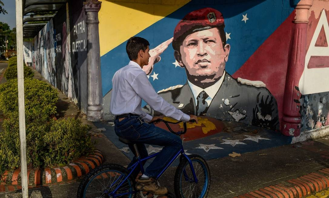 Cidadão venezuelano passa em frente a grafitti do presidente Hugo Chávez, no estado de Barinas: de acordo com estudo, assassinatos no país superar Honduras e El Salvador Foto: FEDERICO PARRA / AFP