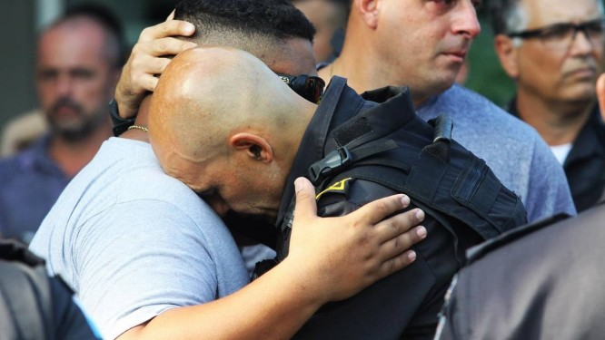 Colegas se emocionam durante o enterro do PM Raphael de Oliveira Monteiro, morto quando fazia patrulhamento na Avenida Pastor Martin Luther King Foto: Paulo Nicolella / Agência O Globo