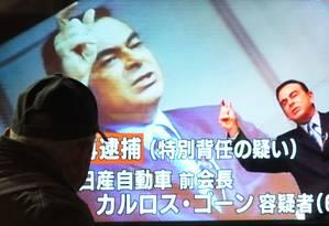 Esta foto tirada no dia 21 de dezembro mostra pedestres olhando para um programa de notícias sobre a situação do ex-presidente Nissan Carlos Ghosn Foto: KAZUHIRO NOGI / AFP