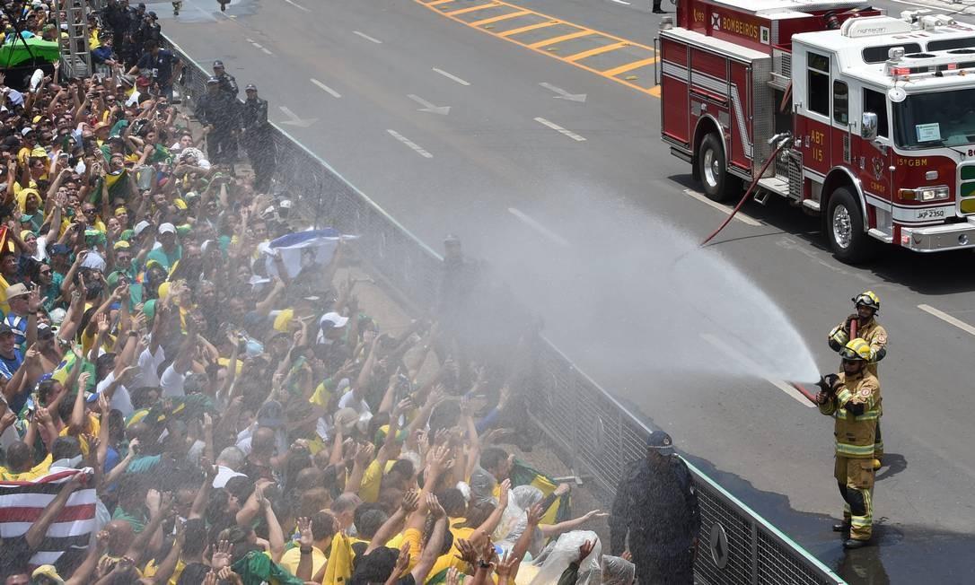 Bombeiros refrescam o público aglomerado para ver a passagem do novo presidente Foto: EVARISTO SA / AFP