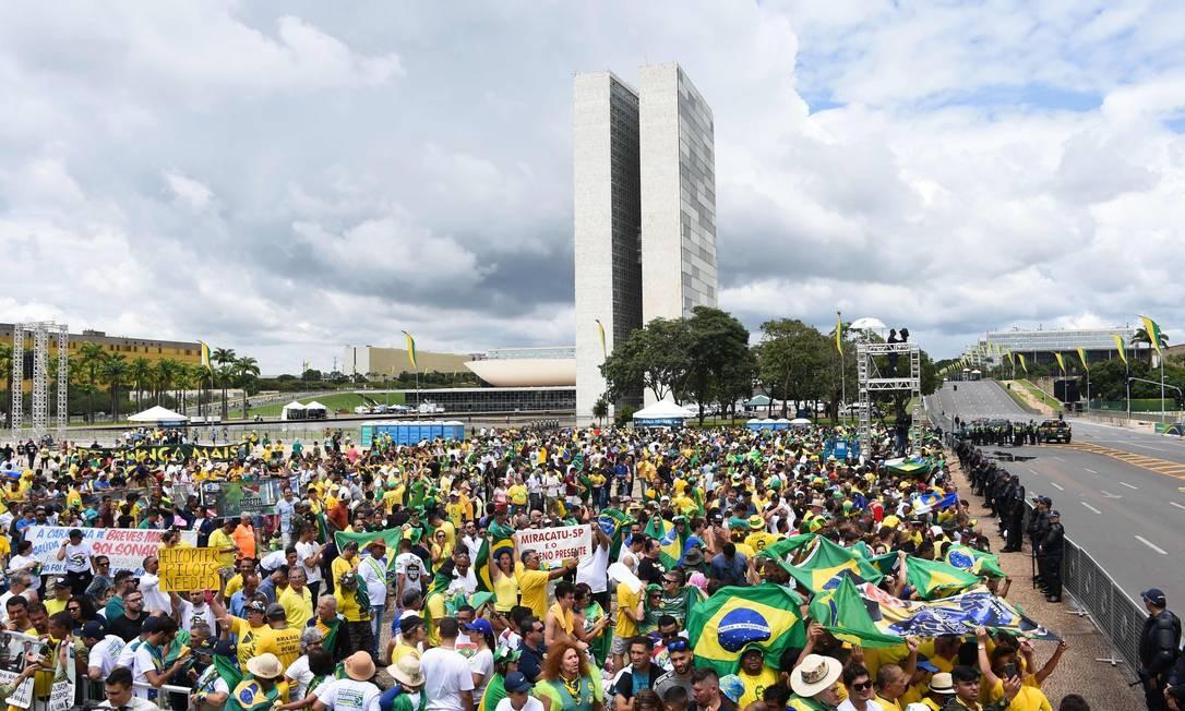 Na Praça dos Três Poderes, apoiadores de Bolsonaro acompanham a cerimônia de posse Foto: EVARISTO SA / AFP